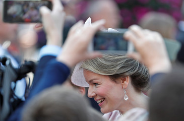 People use their mobile phones to photograph and film Belgium's Queen Mathilde outside the Sainte-Gudule cathedral after a religious service on Belgian national day in Brussels