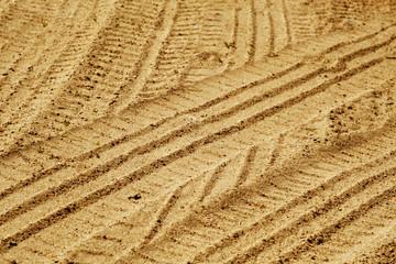Tire imprints on sandy desert road.