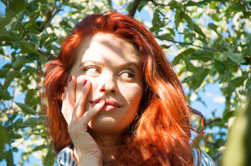 Redhaired girl lying on a branch of tree