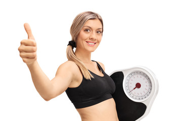 Young woman with a weight scale making thumb up gesture