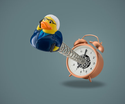 rubber duck business man on spring coming out of alarm clock