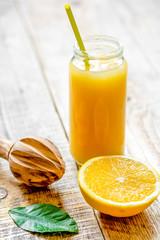 freshly squeezed orange juice in glass bottle on wooden backgrou