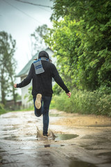 girl runs through puddles in rainy summer weather. A country landscape.