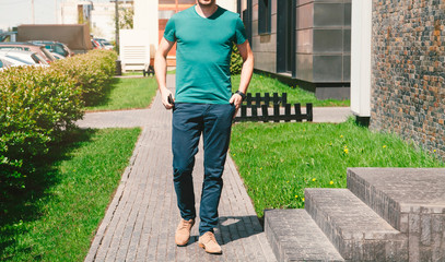 Summer day. Front view. Young man in a green T-shirt and blue pants comes with a phone in his hand, street on a background. Cropped image. Mock up.
