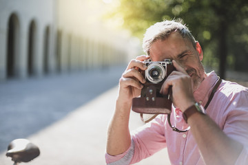 Man taking pictures with an old-fashioned camera in a park