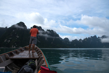 A man standing on head of boat for cruising in lake and see view of beautiful mountains and mist.