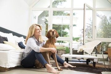 Relaxed woman sitting with her dog on floor of the living room