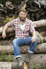 Portrait of bearded man sitting on stack of wood