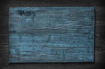 Blue wooden board on a dark wooden background