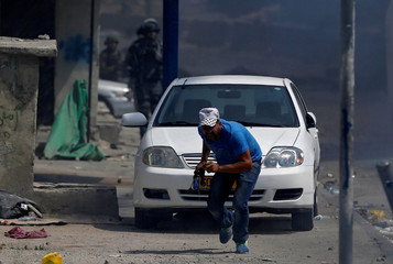 A Palestinian protester runs for cover during clashes with Israeli troops near Qalandiya checkpoint near the West Bank city of Ramallah