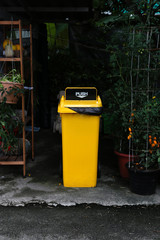 Yellow trash bin with garbage lid on top.