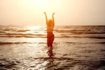Free woman enjoying freedom feeling happy in the sea at sunset.