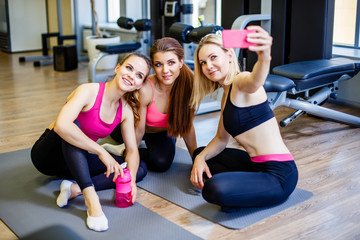 Happy young girls in sportswear taking selfie in gym. Three female friends in healthclub taking selfie with mobile phone.