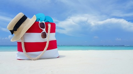 P00155 Maldives white sandy beach bag hat sunglasses and flipflops on sunny tropical paradise island with aqua blue sky sea ocean 4k