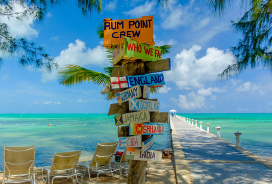 Colorful signpost by the Caribbean sea and a jetty at Rum Point, Grand Cayman, Cayman Islands