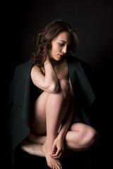 Sensual brunette lady in warm coat in the dark at studio