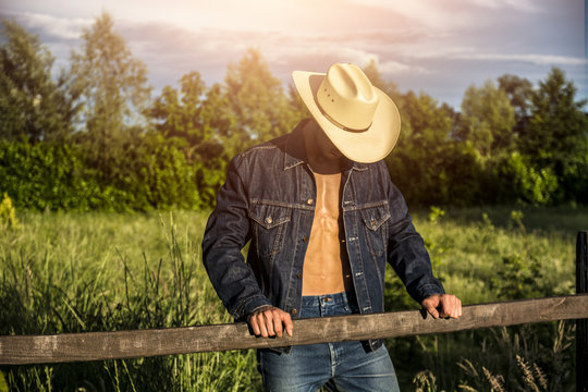 Portrait of sexy farmer or cowboy in hat with unbuttoned shirt on muscular torso, looking down, while standing next to hay field in countryside