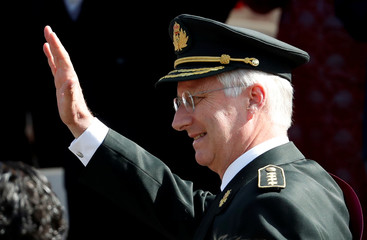 Belgium's King Philippe waves as he leaves after the traditional military parade in front of the Royal Palace on Belgian national day in Brussels