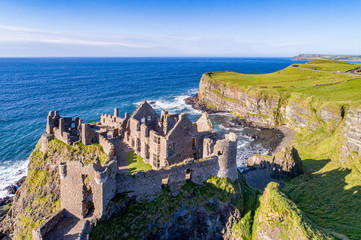 Ruins of medieval Dunluce Castle, cliffs, bays and peninsulas. Northern coast of County Antrim, Northern Ireland, UK. Aerial view. Fototapete