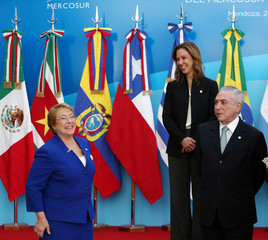 Chile's President Michelle Bachelet smiles next to Brazil's President Michel Temer and Colombia's Commerce, Industry and Tourism Minister Maria Claudia Lacouture before the official photo at the Mercosur trade bloc summit in Mendoza