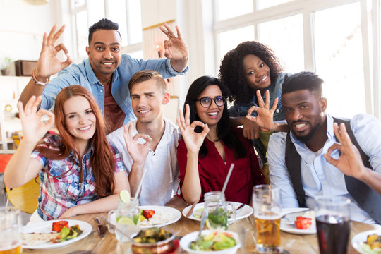 happy friends showing ok hand sign at restaurant