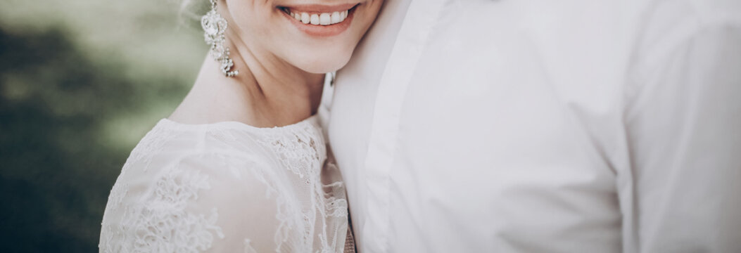 stylish wedding bride smiling. modern bride hugging groom, lips and earrings close up. fine art wedding photo, romantic moment, long edge