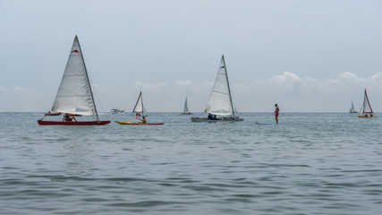 Rest on sea. Sea kayak, boats with sail, catamaran, stand up paddler. Outdoor sea sporting activity