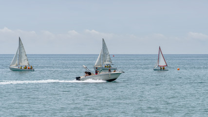Rest on sea. Motor boat, boats with sail. Outdoor sea sporting activity