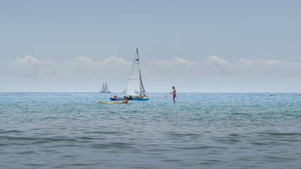 Rest on sea. Sea kayak, boats with sail, stand up paddler. Outdoor sea sporting activity