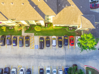 Aerial view of apartment garage with covered parking lots, cars and green trees at multi-floor buildings complex in Humble, Texas, US early morning. Urban infrastructure and transportation concept.