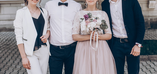 stylish wedding bride with bouquet and groom taking photo with family with bridesmaid and groomsmen after official wedding ceremony