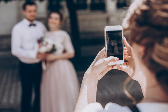 woman taking photo on phone of stylish wedding bride and groom posing. photo booth. wedding couple making photos with friends on phone camera. hand holding smartphone