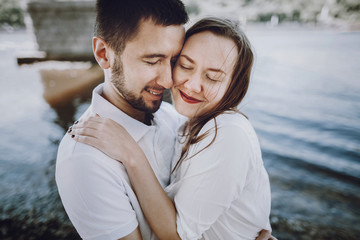 happy stylish couple in love hugging on the beach in  summer city. modern woman and man in fashionable white clothes embracing at the water, romantic sensual moment