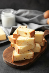 Wooden board with delicious sliced butter cake on table