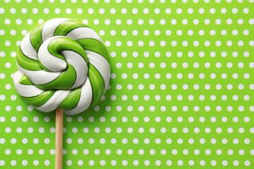 Tasty spiral lollipop on patterned color background