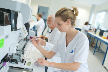 Laboratory team at work, woman in foreground