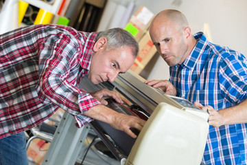 men repairing a machine