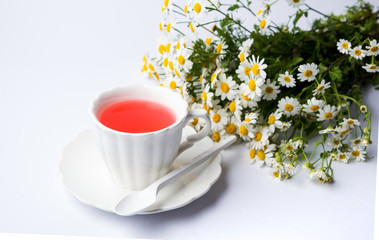 Chamomile flowers and a cup of tea