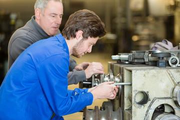 supervisor watching trainee work on machine