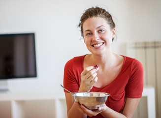 Smiling Young Woman Eating Raspberries