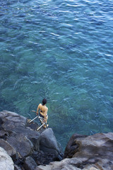 Woman in bathing suit stands on ladder at the edge of rocky ocean shore