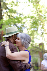 Creative senior couple dancing outdoors