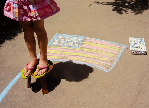 Little girl standing on a bench above a chalk flag for Memorial Day