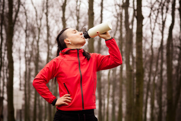 Woman drinking water after jogging in the park.