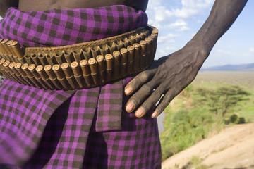 Karo Tribesman wearing a belt of bullets,  Lower Omo Valley, Ethiopia, Africa.