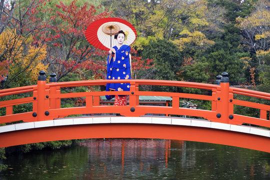 Asia, Japan, Honshu, Kansai Region, Kyoto, Geisha holding an ornate red paper umbrella standing on a traditional style Japanese red bridge