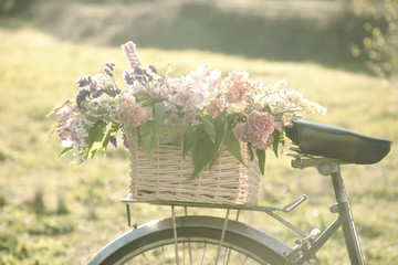 Vintage bicycle on the field with a basket of flowers