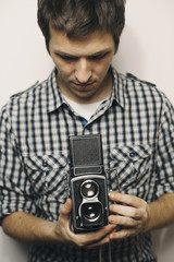 Young man holding retro analog camera