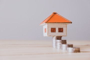 paper house with key on wooden wall background
