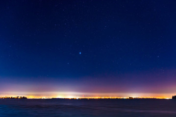 mist and a starry sky above the lights of a city skyline on the waterfront in Auckland, New Zealand